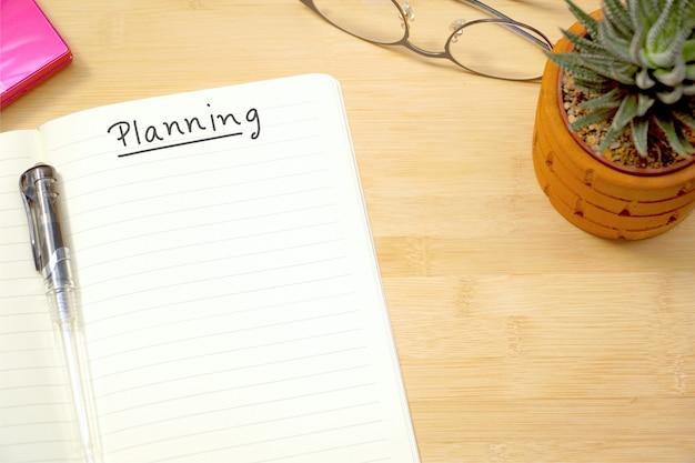"""Widok z góry pustego notatnika z napisem """"planowanie"""" na obszarze roboczym w biurze."""