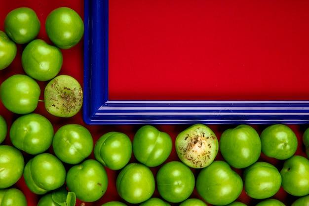Widok z góry pustej ramki na zdjęcia z kwaśnymi zielonymi śliwkami ułożonymi wokół na czerwonym stole z miejsca kopiowania