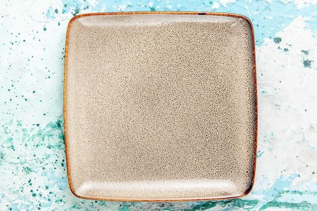 Widok z góry pusty brązowy talerz kwadratowy utworzony na jasnoniebieskim tle kuchnia talerz sztućców