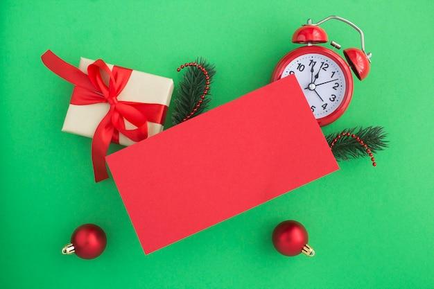 Widok z góry pusty czerwony papier na pozdrowienia i skład boże narodzenie na zielonym tle