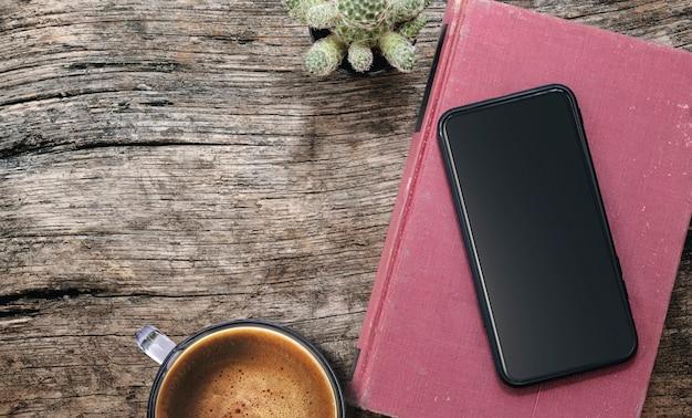 Widok z góry pusty ekran smartfona na czerwoną książkę i filiżankę kawy na drewnianym stole
