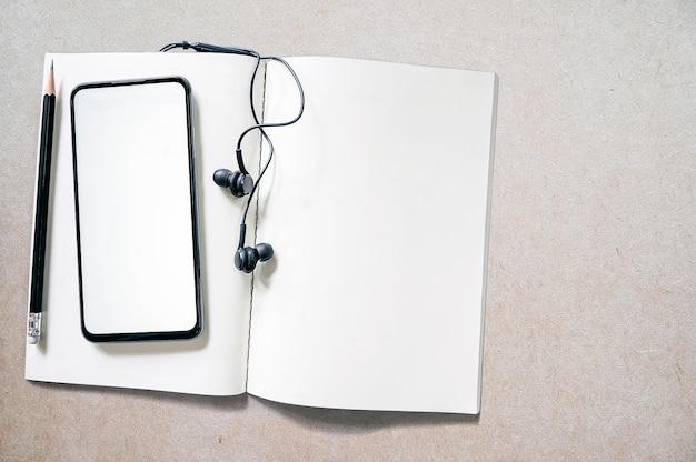 Widok z góry pusty ekran smartfona na otwartym notatniku.