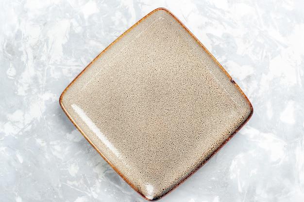 Widok z góry pusty kwadratowy talerz brązowy ed na białej powierzchni