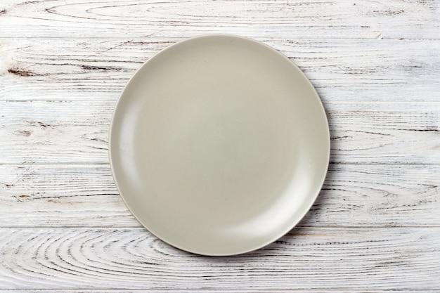 Widok z góry pusty matowy talerz na prosty drewniany stół. widok z góry