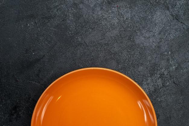Widok z góry pusty pomarańczowy talerz szklany wykonany na ciemnej powierzchni
