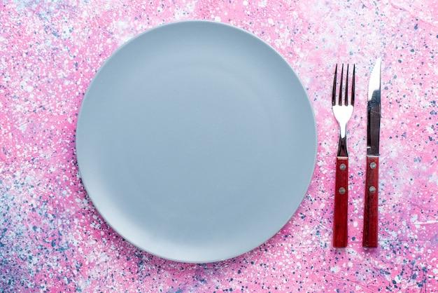 Widok z góry pusty talerz w kolorze niebieskim na jasnoróżowym kolorze stołu ze zdjęciami
