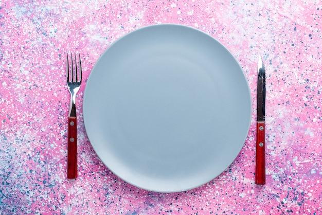 Widok z góry pusty talerz w kolorze niebieskim z widelcem i nożem na jasnoróżowej ścianie