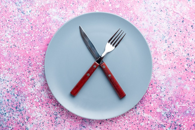 Widok z góry pusty talerz w kolorze niebieskim z widelcem i nożem na różowej ścianie talerz ze zdjęciami sztućce do żywności