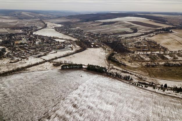 Widok z góry pustych śnieżnych pól i drzewiastych wzgórz na pochmurnym niebie. lotnicze fotografie dronów, zimowy krajobraz.