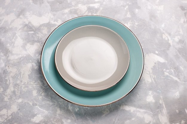 Widok z góry pustych talerzy ze szkła na jasnobiałej powierzchni