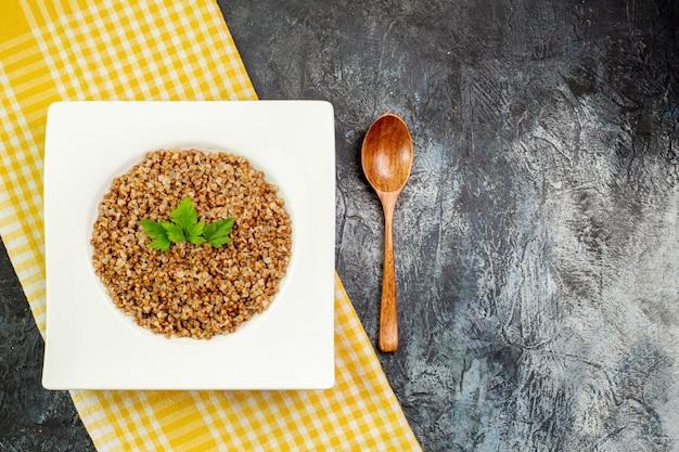 Widok z góry pyszna gotowana kasza gryczana wewnątrz białego talerza na jasnoszarym tle kaloryczny posiłek kolor zdjęcie danie fasola jedzenie wolne miejsce