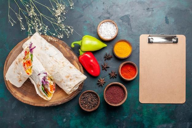 Widok z góry pyszna kanapka mięsna z mięsa grillowanego na rożnie pokrojona w plasterki z notatnikiem i przyprawami na niebieskim biurku burger posiłek mięsny obiad kanapka jedzenie