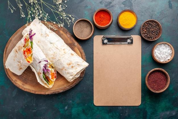 Widok z góry pyszna kanapka mięsna z mięsa grillowanego na rożnie pokrojona w plasterki z przyprawami i notatnikiem na niebieskim biurku burger posiłek mięsny kanapka na lunch