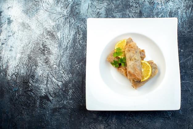 Widok z góry pyszna kapusta dolma z cytryną wewnątrz talerz na ciemnym tle kuchnia obiad kolor lodu posiłek danie chleb kaloria