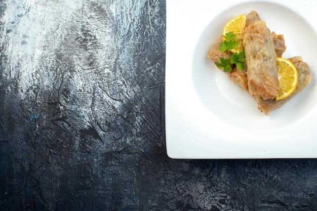 Widok z góry pyszna kapusta dolma z cytryną wewnątrz talerz na ciemnym tle kuchnia obiad lód kolor posiłek chleb jedzenie kaloria