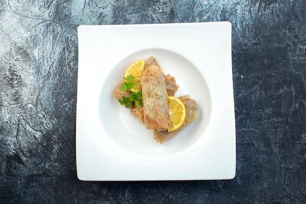 Widok z góry pyszna kapusta dolma z cytryną wewnątrz talerz na ciemnym tle kuchnia obiad lód kolor posiłek danie chleb jedzenie kaloria