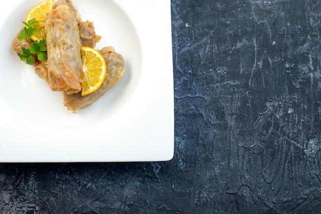 Widok z góry pyszna kapusta dolma z cytryną wewnątrz talerz na ciemnym tle kuchnia obiad lód kolor posiłek danie jedzenie kaloria