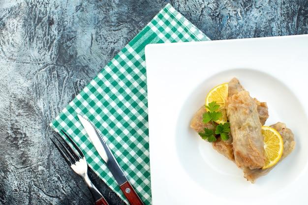 Widok z góry pyszna kapusta dolma z cytryną wewnątrz talerz na ciemnym tle kuchnia obiad posiłek jedzenie kaloria danie kolor chleb