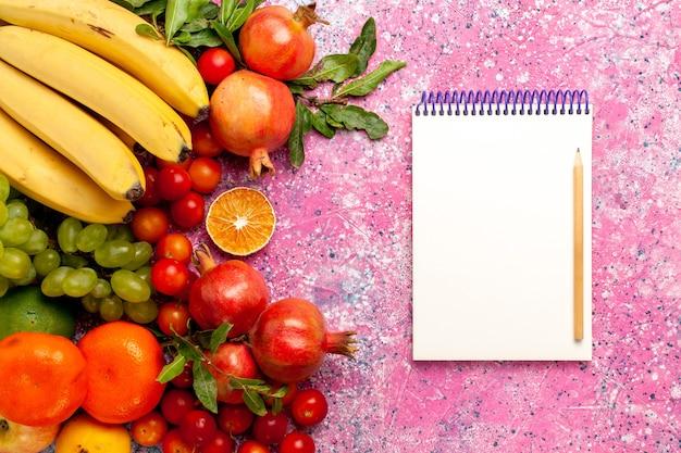 Widok z góry pyszna kompozycja owoców na jasnoróżowym biurku
