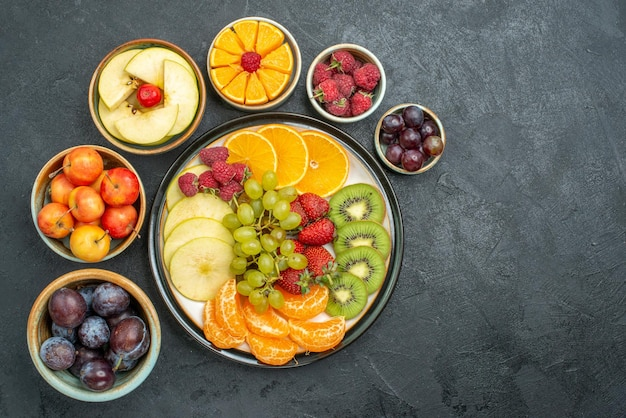 Widok z góry pyszna kompozycja owocowa świeże i pokrojone owoce na ciemnym tle dojrzałe świeże owoce zdrowej diety łagodne