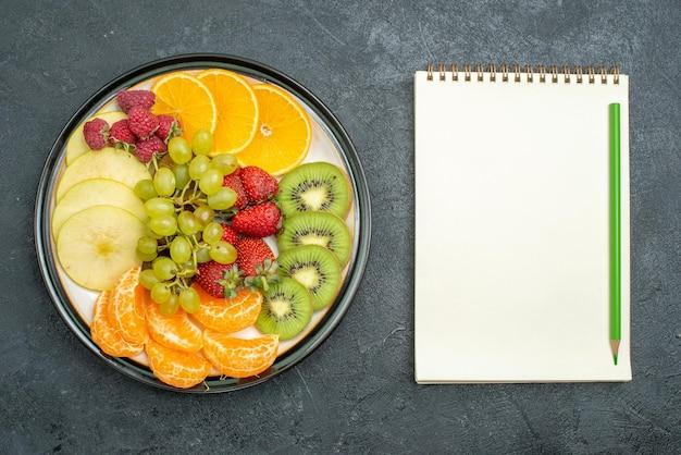 Widok z góry pyszna kompozycja owocowa świeże pokrojone i aksamitne owoce na ciemnym tle dojrzałe świeże, łagodne owoce diety zdrowej