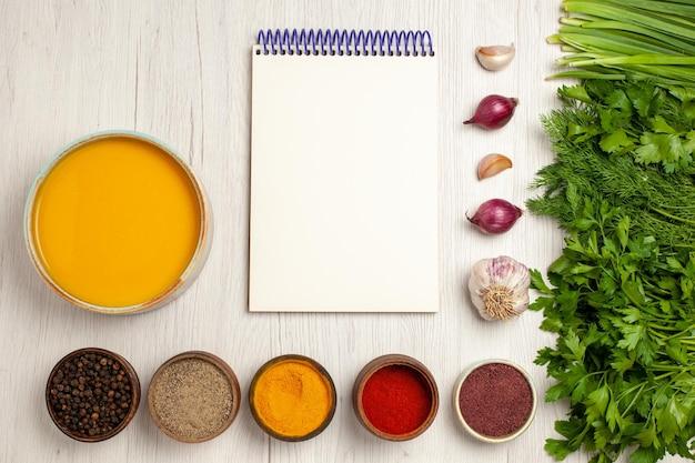 Widok z góry pyszna kremowa zupa z zieleniną i przyprawami na białym biurku z sosem do zupy z kremem obiadowym daniem