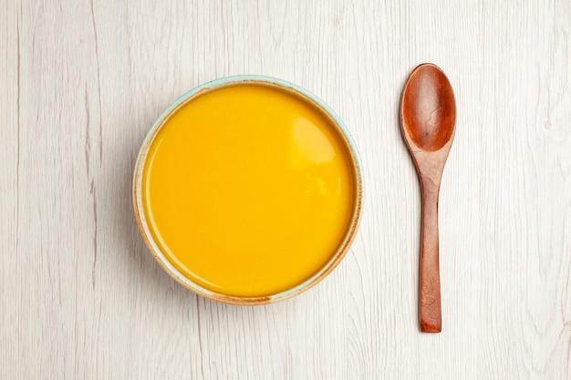 Widok z góry pyszna kremowa zupa żółta kolorowa zupa na białym biurku zupa sos posiłek kremowy obiad danie