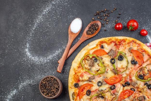 Widok z góry pyszna pizza z serem z czerwonymi pomidorami na ciemnej powierzchni