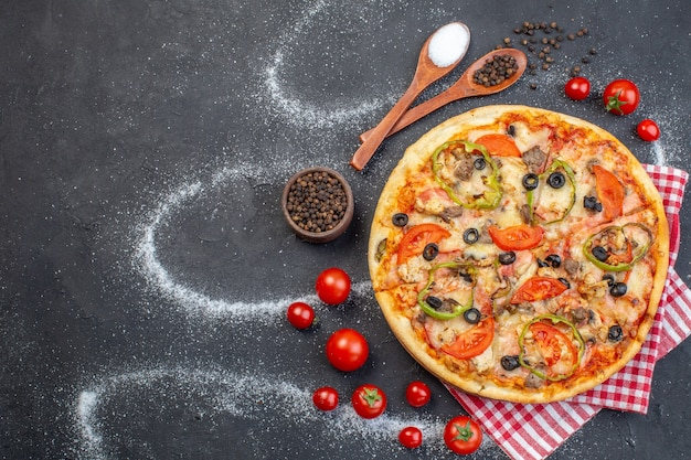 Widok z góry pyszna pizza z serem z czerwonymi pomidorami na ciemnym tle