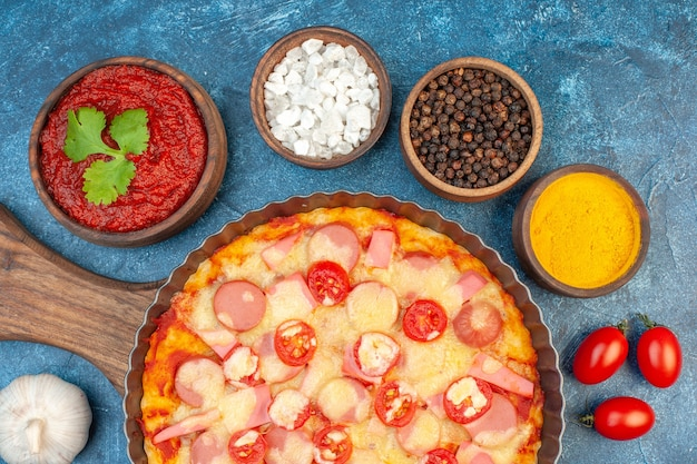 Widok z góry pyszna pizza z serem z przyprawami i pomidorami na niebieskim tle włoskie jedzenie ciasto ciasto fast-food kolor zdjęć