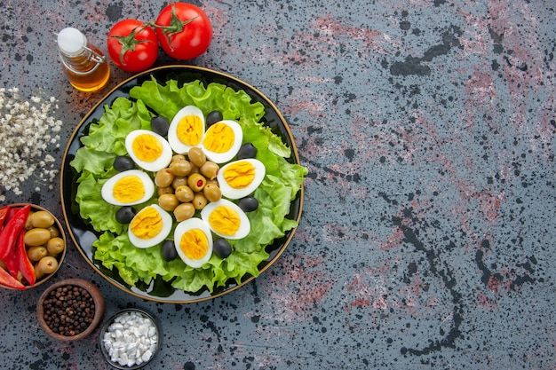 Widok z góry pyszna sałatka jajeczna z pomidorami i oliwkami na jasnym tle