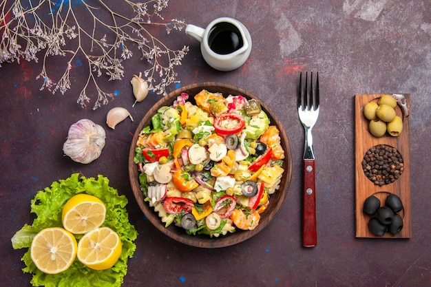 Widok z góry pyszna sałatka jarzynowa z plasterkami cytryny i zieloną sałatą na ciemnym tle posiłek dieta sałatka zdrowie