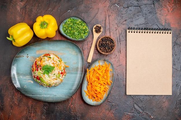 Widok z góry pyszna sałatka jarzynowa z zieleniną i marchewką na ciemnym tle kolor dojrzałe jedzenie posiłek zdrowe życie zdjęcie
