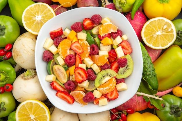 Widok z góry pyszna sałatka owocowa wewnątrz talerza ze świeżymi owocami na szarym drzewie owocowym egzotyczna tropikalna fotografia dojrzała dieta
