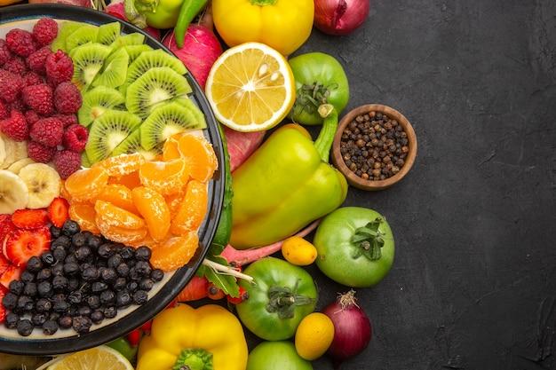 Widok z góry pyszna sałatka owocowa wewnątrz talerza ze świeżymi owocami na szarym tropikalnym drzewie owocowym egzotyczna dojrzała dieta zdjęcie