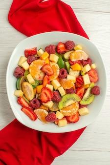 Widok z góry pyszna sałatka owocowa z czerwoną tkanką na białym cytrusowym egzotycznym owocowym jagodzie dojrzałe łagodne zdjęcie