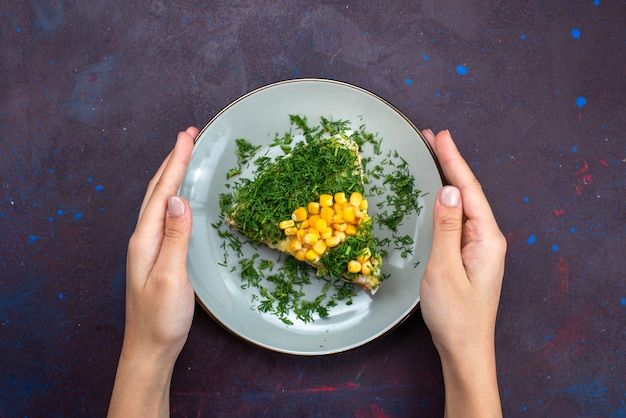 Widok z góry pyszna sałatka z majonezem, kukurydzą i kurczakiem wewnątrz talerza na ciemnej podłodze.
