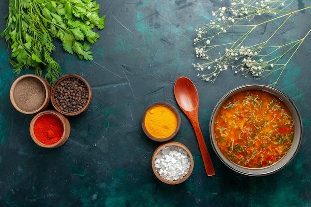Widok z góry pyszna zupa jarzynowa z różnymi przyprawami na ciemnozielonej powierzchni produkt spożywczy posiłek składnik zupa jarzynowa