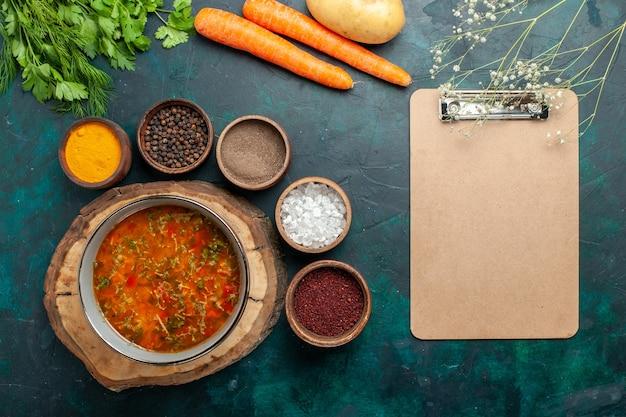 Widok z góry pyszna zupa jarzynowa z różnymi przyprawami na ciemnozielonej powierzchni żywność składniki warzywne zupa produkt posiłek