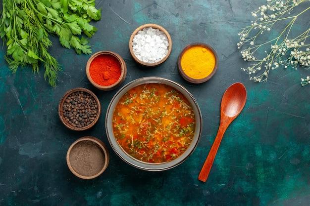 Widok z góry pyszna zupa jarzynowa z różnymi przyprawami na szarym biurku posiłek zupa jarzynowa składnik produktu