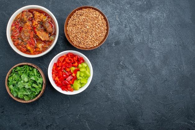 Widok z góry pyszna zupa jarzynowa z surową kaszą gryczaną i zieleniną na szarej przestrzeni