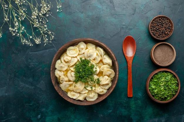 Widok z góry pyszna zupa kluskowa z różnymi przyprawami i zieleniną na zielonej powierzchni zupa mięsna ciasto warzywne
