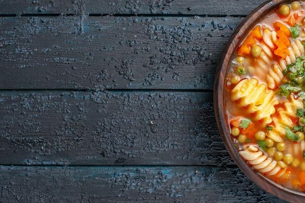 Widok z góry pyszna zupa makaronowa z zieleniną i warzywami wewnątrz talerza na ciemnym daniu na biurku włoski sos obiadowy zupa makaronowa