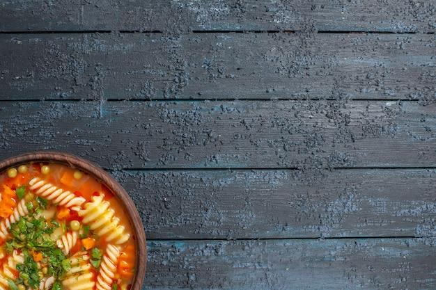 Widok z góry pyszna zupa makaronowa z zieleniną i warzywami wewnątrz talerza na ciemnym tle danie włoski posiłek zupy makaronowej