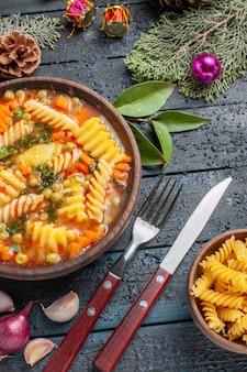 Widok z góry pyszna zupa makaronowa ze spiralnego włoskiego makaronu na ciemnoniebieskiej podłodze danie kuchnia kolorowa zupa makaron