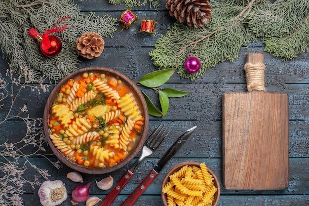 Widok z góry pyszna zupa makaronowa ze spiralnego włoskiego makaronu na ciemnoniebieskim biurku danie kuchnia kolorowa zupa makaron