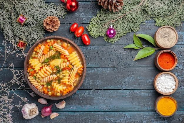 Widok z góry pyszna zupa makaronowa ze spiralnego włoskiego makaronu na ciemnoniebieskim rustykalnym biurku kuchnia zupa makaronowa kolorowa potrawa