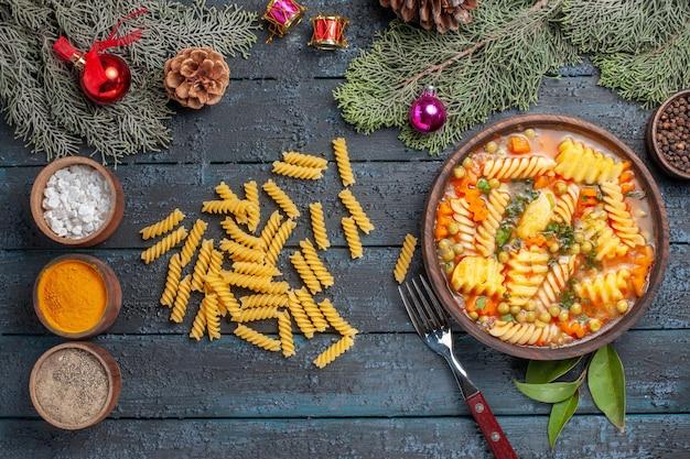 Widok z góry pyszna zupa makaronowa ze spiralnego włoskiego makaronu z przyprawami na ciemnoniebieskim biurku danie kuchnia kolorowa zupa makaron