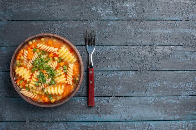 Widok z góry pyszna zupa makaronowa ze spiralnego włoskiego makaronu z zielenią na ciemnym rustykalnym daniu obiadowym na biurku włoski sos do zupy makaronowej