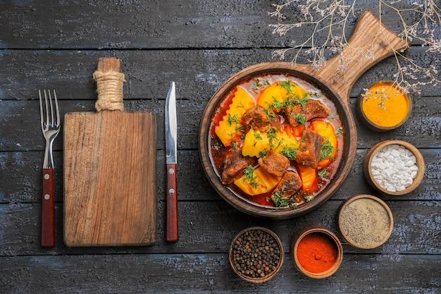 Widok z góry pyszna zupa mięsna z ziemniakami i zieleniną na ciemnym biurku